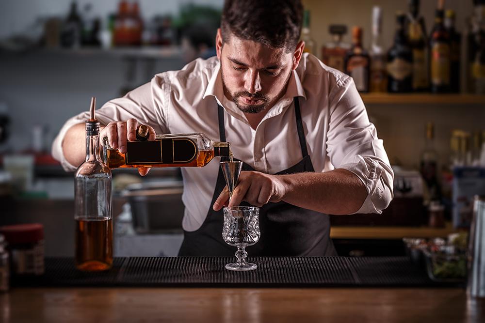 ウイスキーを計量するバーテンダー