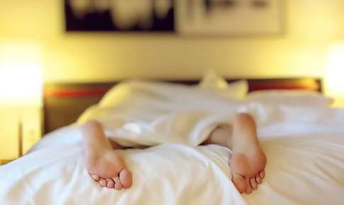 ベッドで眠る女性の足