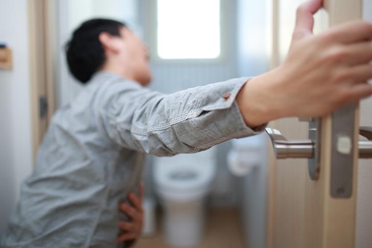 二日酔いでトイレに駆け込む男性