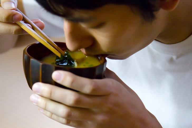 味噌汁を飲む男性