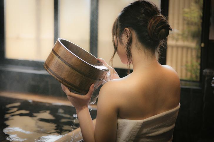 風呂桶をかけ流しする女性